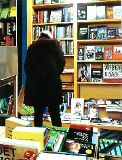catalogue- hyperrealism painting by artist Gerard Boersma showing woman behind computer searching books in public library leeuwarden