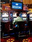 Las Vegas Slot Machines- stores and interiors- hyperrealism  painting of man hitting the slot machines in Las Vegas hotel lobby by artist Gerard Boersma