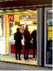 Smullers- hyperrealism public transport painting of people women waiting in line at kiosk on central train station in Zwolle by artist Gerard Boersma